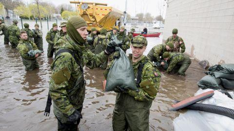 Canadian Forces personnel unload sandbags in Deux-Montagnes, Quebec.