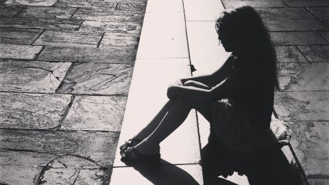 Silhouette of girl sitting on steps, New Orleans, Louisiana