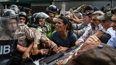 Opposition activists scuffle with riot police in Caracas on May 12.