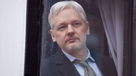 """WikiLeaks founder Julian Assange is seen through the window of the door leading to the balcony of the Ecuadorian embassy in central London on February 5, 2016 from where he addressed the media. During a press conference on February 5 Julian Assange, speaking via video-link, called for Britain and Sweden to """"implement"""" a UN panel finding saying that he should be able to walk free from Ecuador's embassy, where he has lived in self-imposed confinement since 2012. / AFP / BEN STANSALL        (Photo credit should read BEN STANSALL/AFP/Getty Images)"""