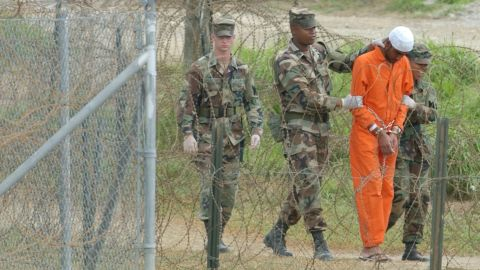 """A detainee is escorted by military police at the US naval base in Guantanamo Bay, Cuba, on February 6, 2002. The base's detention facilities had been repurposed to hold detainees from the US """"war on terror."""""""