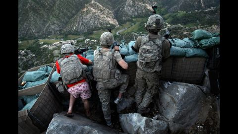 """US soldiers take defensive positions after receiving fire from Taliban positions in Afghanistan's Kunar Province on May 11, 2009. Army Spc. Zachary Boyd, left, was wearing """"I love NY"""" boxer shorts after rushing from his sleeping quarters to join his fellow platoon members."""