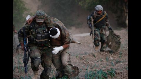 An Afghan soldier carries his wounded colleague to a US Army helicopter after a roadside bomb attack on the outskirts of Kandahar, Afghanistan, on July 29, 2011.
