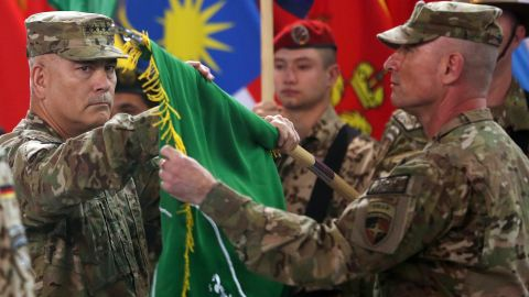 """US Army Gen. John Campbell, left, and Command Sgt. Maj. Delbert Byers open the """"Resolute Support"""" flag during a ceremony in Kabul on December 28, 2014. The United States and NATO formally ended the combat mission in Afghanistan. Resolute Support was the name of the new mission to assist and train Afghanistan's troops."""