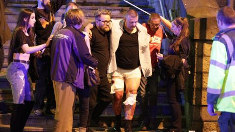 An injured man is helped at the scene.