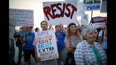 Israeli and American activists hold signs Monday, May 22, during an anti-Trump protest next to the US embassy in Tel Aviv, Israel.