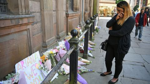 A woman looks emotional as she looks at flowers left in St Ann Square on Tuesday, May 23, 2017 in Manchester,England. At least 22 people were killed in a suicide bombing at a pop concert packed with children in the northern English city of Manchester, in the worst terror incident on British soil since the London bombings of 2005.