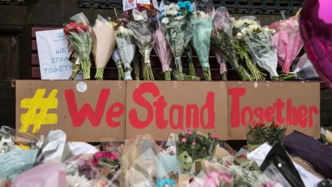 """Floral tributes and a message that reads """"We Stand Together"""" are pictured in Albert Square in Manchester, northwest England on May 24, 2017, left as tributes to the victims of the May 22 terror attack at the Manchester Arena. Police on Tuesday named Salman Abedi -- reportedly British-born of Libyan descent -- as the suspect behind a suicide bombing that ripped into young fans at an Ariana Grande concert at the Manchester Arena on May 22, as the Islamic State group claimed responsibility for the carnage. / AFP PHOTO / CHRIS J RATCLIFFE        (Photo credit should read CHRIS J RATCLIFFE/AFP/Getty Images)"""