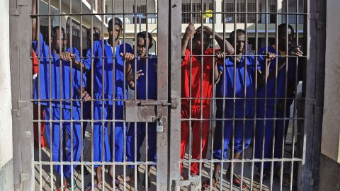 Somali prisoners convicted of piracy, stand behind a gate of the prison in Garowe, Puntland state, in northeastern Somalia, on December 14, 2016.<br />However, security firms complain that pirates are receiving light sentences that do not deter them from repeat offenses.