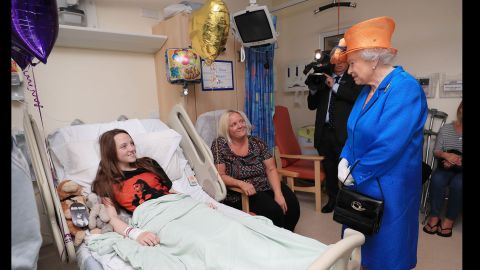 """Britain's Queen Elizabeth II speaks to 15-year-old Millie Robson and her mother, Marie, during <a href=""""http://edition.cnn.com/2017/05/25/europe/queen-elizabeth-manchester-attack/index.html"""" target=""""_blank"""">a visit to the Royal Manchester Children's Hospital</a> on May 25. The Queen was visiting those injured in the attack."""