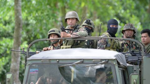 Philippine soldiers ride in the back of a truck as they leave a military camp in Marawi, on the southern island of Mindanao on May 25, 2017, to reinforce soldiers at the battlefront in the city centre days after Muslim extremists attacked the city. Philippine troops aboard helicopters and in armoured tanks battled Islamist militants inside a southern city on May 25, as reports emerged of the gunmen murdering civilians. / AFP PHOTO / TED ALJIBE        (Photo credit should read TED ALJIBE/AFP/Getty Images)