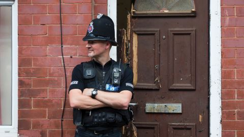 A police officer stands on duty outside a residential property on Lindum Street in Moss Side, Manchester, on May 25, 2017, as their investigations continue into the May 22 terror attack at the Manchester Arena. Britain Thursday closed in on a jihadist network thought to be behind the May 22, 2017 Ariana Grande concert attack, as grief mixed with anger at the US over leaked material from the probe. Britain has raised its terror alert to the maximum level and ordered troops to protect strategic sites after 22 people were killed in a suicide bomb attack on a Manchester pop concert. / AFP PHOTO / JON SUPER        (Photo credit should read JON SUPER/AFP/Getty Images)
