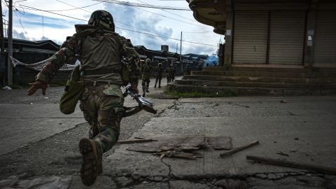 MARAWI CITY, PHILIPPINES - MAY 25: Soldiers run for cover to evade sniper fire while trying to clear the city of armed militants, one street at a time, on May 25, 2017 in Marawi city, southern Philippines. Gun battles between ISIS-linked militants and Filipino troops erupted in Marawi city on Tuesday when gunmen from the local terrorist groups Maute Group and Abu Sayyaf rampaged through the southern city, prompting President Rodrigo Duterte to declare 60 days of martial law in Mindanao. Thousands of residents were reported to have fled from Malawi city while at least 21 people were killed, including a police chief who had been beheaded and buildings were torched by the terror groups. President Duterte said the influence of Islamic State is one of the nation's top security concerns, and martial law on Mindanao island could be extended across the Philippines to enforce order, allowing the detention of people without charge. (Photo by Jes Aznar/Getty Images)