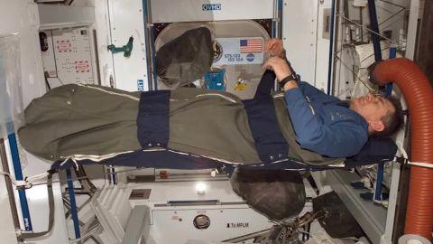 An astronaut sleeps aboard the International Space Station.