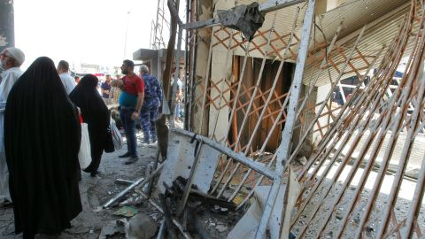 Iraqis gather at the site of a car bomb explosion near Baghdad's Retirement Department.