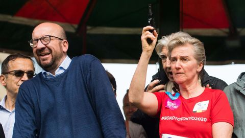 Belgian Prime Minister Charles Michel reacts as Princess Astrid of Belgium fires a starter's pistol signaling the start of a 20K road race Sunday in Brussels.