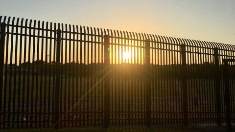The sun sets through fencing along the Mexican border in Eagle Pass, Texas.