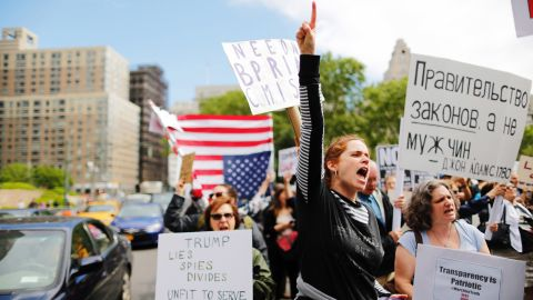"""Demonstrators take part in an anti-Trump """"March for Truth"""" rally at Foley Square on June 3, 2017 in New York City. The sign in Russian reads, """"Government of Laws, not men"""" - John Adams."""