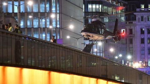 A helicopter flies near London Bridge.