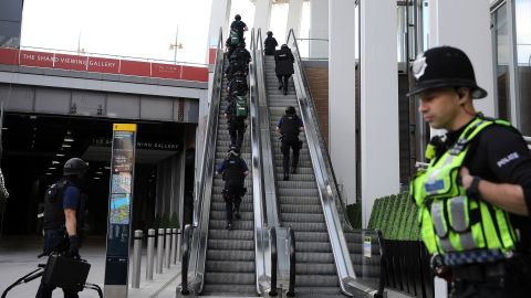 Counter terrorism officers move up an escalator under The Shard, an iconic highrise near the scene of last night's London Bridge attack.