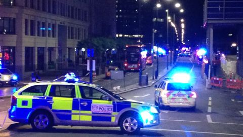 """TOPSHOT - A photograph taken on a mobile phone shows British police cars blocking the entrance to London Bridge, in central London on June 3, 2017, following an incident on the bridge.  Police are dealing with a """"major incident"""" on London Bridge, Transport for London said on Saturday, after witnesses reported seeing a van mounting the pavement and hitting pedestrians. / AFP PHOTO / Daniel SORABJI        (Photo credit should read DANIEL SORABJI/AFP/Getty Images)"""