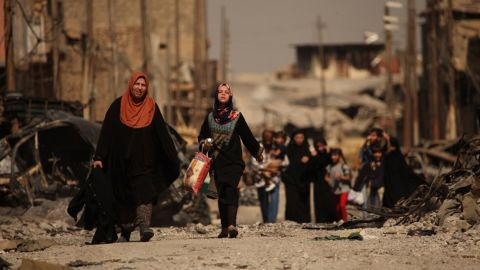 """Iraqi civilians escape the fierce battle raging in the Zinjili neighborhood in western Mosul on June 4, 2017. As these women passed by Iraqi security forces, the woman in the orange hijab screamed, """"Where were you for the last three years?"""""""