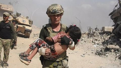 """Dave Eubank from the """"Free Burma Rangers"""" volunteer organization carries a little girl to safety after spotting her hiding under her dead mother's hijab for two days. The child was rescued in western Mosul as gunfire raked the area. Photo courtesy of Free Burma Rangers (www.freeburmarangers.org/)"""