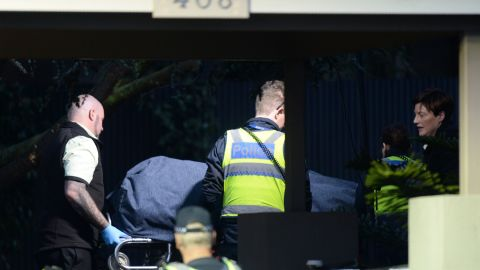 Police officers help the coroner remove a body at the scene on June 6.
