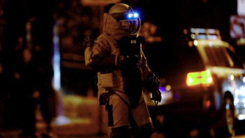 A bomb squad member exits a residential building in Brighton on June 5.