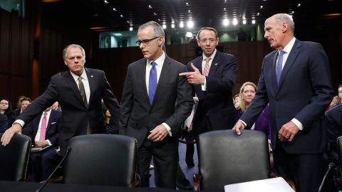 Jim Wolfe, committee staff member, left, helps direct acting FBI Director Andrew McCabe, second left, Deputy Attorney General Rod Rosenstein, and National Intelligence Director Dan Coats to their seats for a Senate Intelligence Committee hearing about the Foreign Intelligence Surveillance Act, on Capitol Hill, Wednesday, June 7, 2017, in Washington. (AP Photo/Alex Brandon)