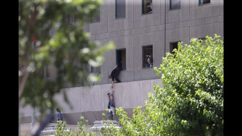 Police help civilians escape the Iranian parliament building Wednesday during twin attacks.