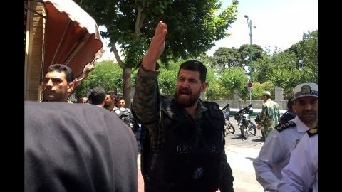 A policeman gestures while officials secure the streets of Tehran as a siege unfolds Wednesday at the parliament building.