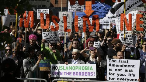 Counterprotesters hold a signs across the street from an anti-Islamic law rally in Seattle.