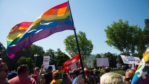 Attendees of the Equality March pass by the White House