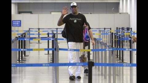 Rodman waves to photographers at Beijing Capital International Airport ahead of his departure to Pyongyang on June 13.