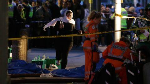 A woman runs near paramedics working near the fire.