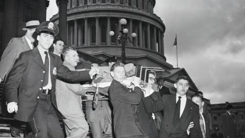 """Rep. Kenneth Roberts shown here being carried down the Capitol steps after Puerto Rican nationalists opened fire in the Capitol Building, shouting """"Free Puerto Rico."""""""