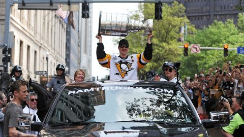 The Penguins' Sidney Crosby hoists the Stanley Cup during a victory parade in Pittsburgh.