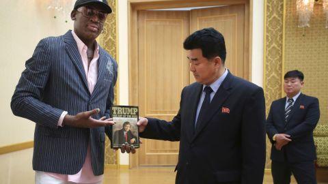 "Former NBA basketball star Dennis Rodman presents a book titled ""Trump The Art of the Deal"" to North Korea's Sports Minister Kim Il Guk Thursday, June 15, 2017, in Pyongyang, North Korea. (AP Photo/Kim Kwang Hyon)"
