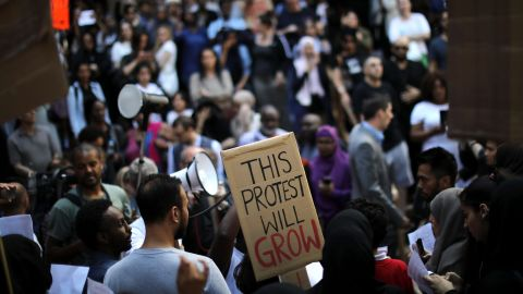 LONDON, ENGLAND - JUNE 16:  Protesters gather outside of Kensington Town Hall on June 16, 2017 in London, England. 30 people have been confirmed dead and dozens still missing after the 24 storey residential Grenfell Tower block in Latimer Road was engulfed in flames in the early hours of June 14. Emergency services will spend a third day searching through the building for bodies. Police have said that some victims may never be identified.  (Photo by Dan Kitwood/Getty Images)