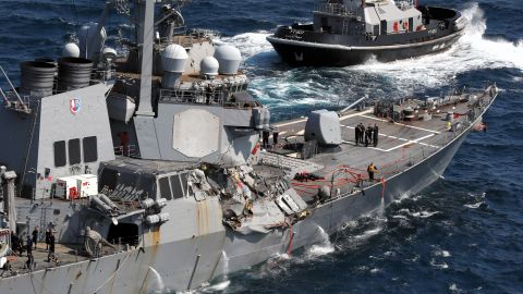 With the help of tug boats, the USS Fitzgerald, with its damaged starboard side, makes its way toward the US Navel base, Yokosuka, after colliding with a Philippines based container ship off the coast of Shimoda, Japan on June 17. Seven U.S. Navy crew members are missing and three, including captain, were injured.