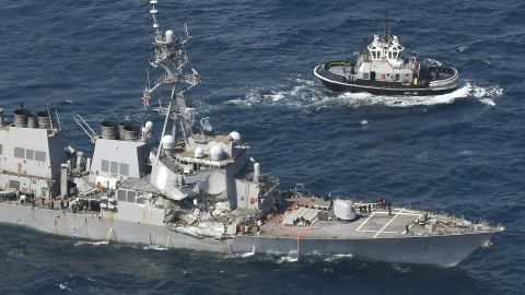 The USS Fitzgerald heads to Yokosuka Naval Base after a collision with a container ship on Saturday.
