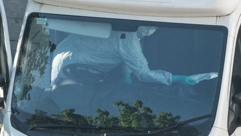 A forensics officer examines the interior of a van.