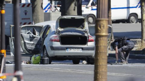 """A bomb disposal police officer (R)checks a car in a sealed off area on the Champs-Elysees avenue in Paris, on June 19, 2017 after a car crashed into a police van before bursting into flames, with the driver being armed, probe sources said.  A source close to the investigation said the driver was """"seriously injured"""".  / AFP PHOTO / Thomas SAMSON        (Photo credit should read THOMAS SAMSON/AFP/Getty Images)"""