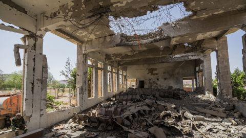 A military guard sits in the former Assembly Hall of the Governor of Saada that now lies in ruins following multiple airstrikes in April 2015.