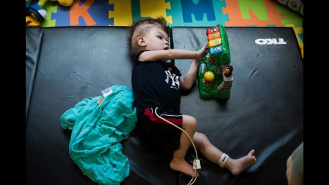 Anias plays with a toy while laying on a mat in his room at Blythedale Children's Hospital.