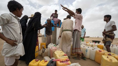 ABS IDP SETTLEMENT,  YEMEN - 6 MAY 2017. Displaced people collect potable water during the one-hour distribution window at midday. Some have lived in tents in the desert for the past two years.Water is heavily rationed and is only available during one-hour windows, which normally take place only three times a day. Giles Clarke/UN OCHA