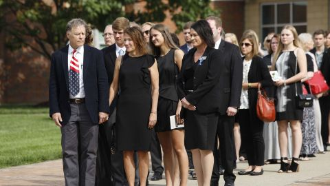 Fred and Cindy Warmbier, left and center, watch as the casket of their son is carried out of his funeral.