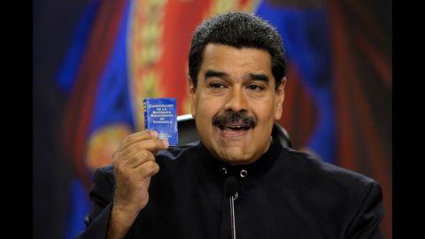 Maduro holds up a copy of the Venezuelan constitution during a news conference at the presidential palace in Caracas on June 22. Maduro has called for changes to the constitution amid the unrest.