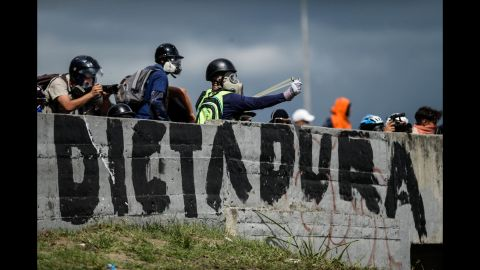 Opposition activists aim projectiles toward riot police during a demonstration on June 19.